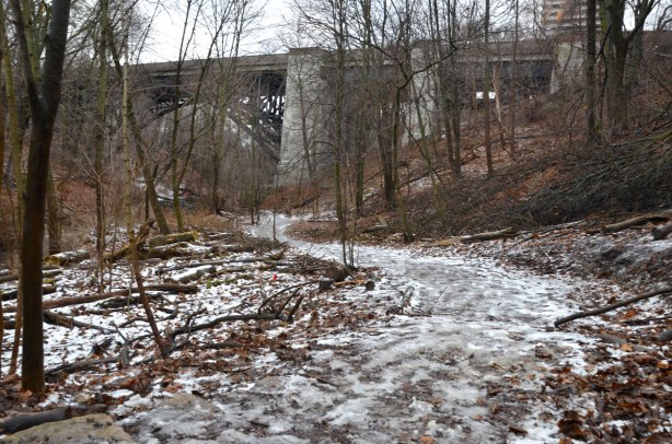 a view of the bridge from a path in the ravine from a short distance away.  It is winter so there is some snow and ice on the path and the trees have no leaves.