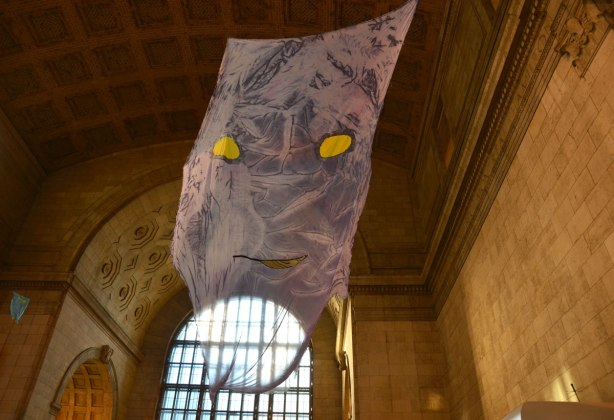 A large translucent rectangular piece of fabric hangs from the ceiling.  It sort of has a face on it, yellow eyes and a small slit mouth.