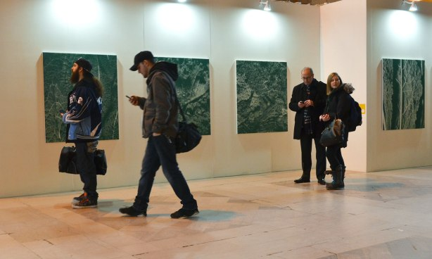 Four people, two are standing together while one texts, and two others are walking past.  Four large square paintings (or photos?) are behind them on a white wall.