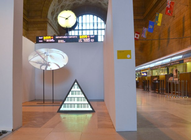 video art installations at an art exhibit.  The large clock and departures board of the train station are seen over the top of the temporary walls of the exhibit.