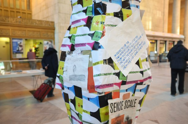 part of a piece of art that is a pillar like structure cover with bits of colourful paper.  There is also a child's drawing in pencil on an 8 by 11 piece of paper.  Also a sign in blue letters that says .  In the background there are a couple of people walking past.