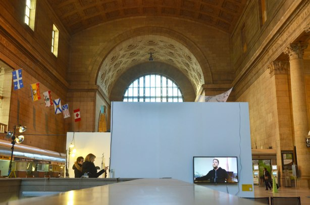 A view of the Great Hall of Union Station with the provincial flags along one wall, the archway over the window at the end of the room, and an art exhibit in the main part of the hall.  Two woman are looking at sculptures on one side.  A video screen is showing a video about the exhibit - a man sitting in a chair is what is seen in this picture.
