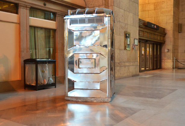 An art piece, a shiny silver coloured porta potty stands in the middle of the floor.  A trash container (real) is behind it.