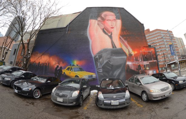 large mural on the side of a building.  A number of cars are parked in front of it.  The mural depicts the bathhouse raids, an event in Toronto's history where police raided gay bath house and arrested those they found inside.  A yellow Toronto police car, a fire truck with its lights on are both in the picture.  An oversized person is in the center, hands held over her/his head.