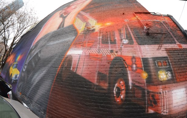 right hand side of the bathhouse raid mural on Church St. showing a firetruck with its red flashing lights on