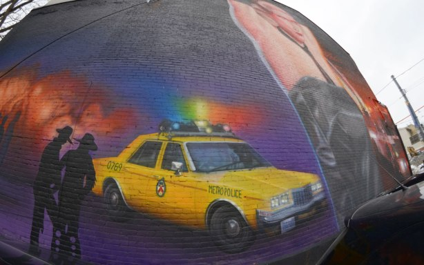 part of a large mural showing a yellow Toronto police car from the 1980's, a couple of policemen and a crowd of men standing just back of the police car