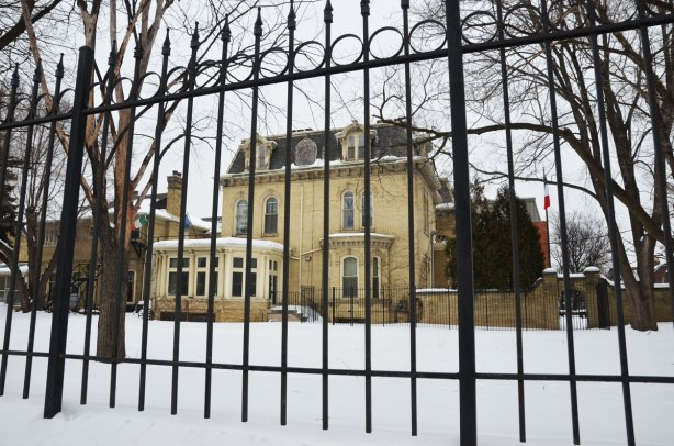 Chudleigh, a large yellow brick house built in 1872, viewed from the side (looking through at the bars of the fence in the foreground.)  Winter time, snow and large trees