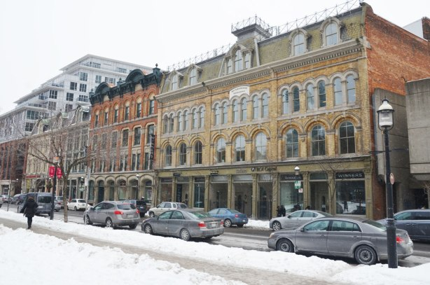 A row of 4 storey brick buildings built in the late 1880's along the south side of Front Street, taken on a winter day with snow on the ground.  Cars parked on the street in front of the builings.  Arched windows, mansard roofs.