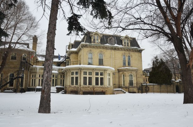 Winter time, snow and large trees.  Chudleigh, a large yellow brick house built in 1872, viewed from the side (looking through the bars of the fence)