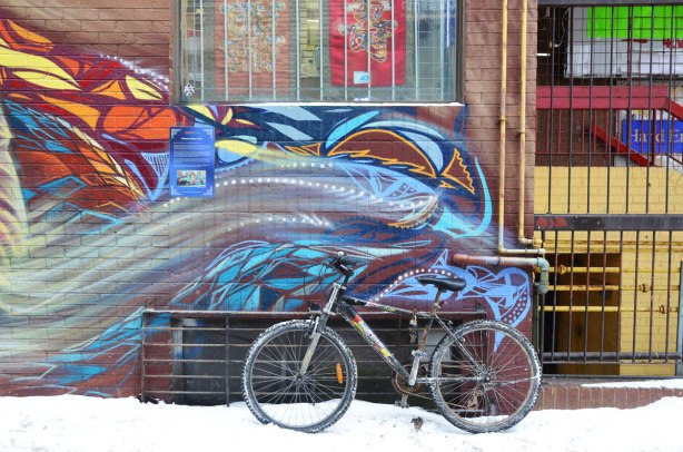 A bike is leaning against a wall of an alley, there is snow on the ground.  On the wall is the right hand end of a long mural