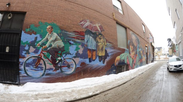 fish eye lens photo of the mural, taken from the left hand side, older man on bicycle is the closest picture on the mural, next are the two people sharing an umbrella.  The remaining parts of the mural are more difficult to discern.  There is a car parked in the alley