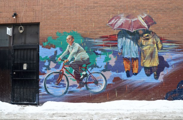 Part of a mural on an alley wall.  There are two parts of the mural visible in this photograph.   An older man is riding a bicycle in one part and twp people are sharing an umrella and walking away from the viewer in the other part
