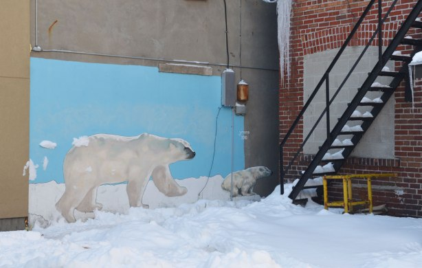 A mural on a wall of two polar bears - an adult and a young cub.  It looks like they are walking on the snow.