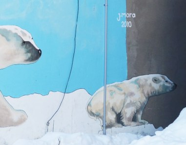 Close up of the mural of two polar bears.  in this picture, the whole cub is visible but only the nose of the adult bear is seen.  The picture is signed J. Mora 2010