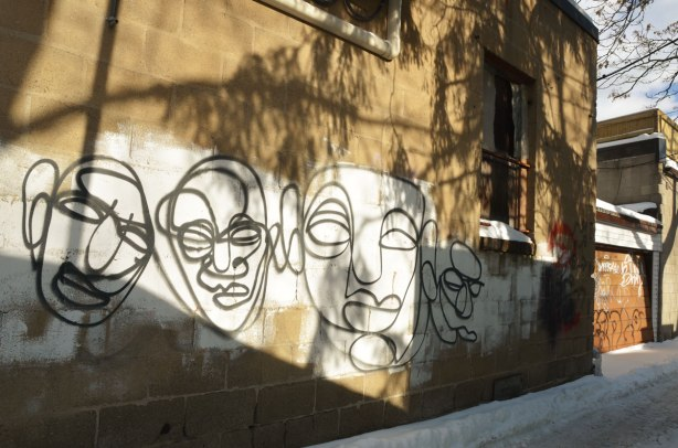 On a brownish grey wall, some white paint has been applied to provide a backgound for some black line drawings of faces.   There are four faces.