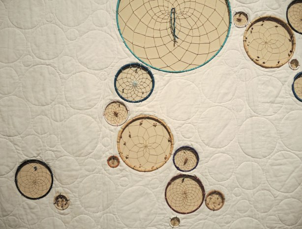 A quilt made of plain beige fabric into which dreamcatchers of various sizes have been incorporated.