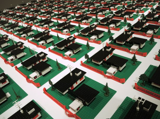 A grid of white lego bungalows with black roofs with detached garages, green lego lawns and red fences.
