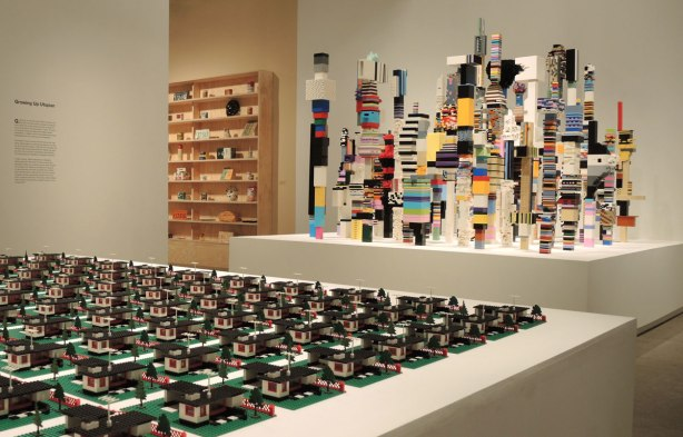 A portion of three Douglas Coupland creations are visible.  In the foreground are numerous lego houses complete with yards and garages all laid out in a grid.  In the background are wood shelves with household articles from the past.  In the middle are lego towers in bright stripes and interesting shapes.