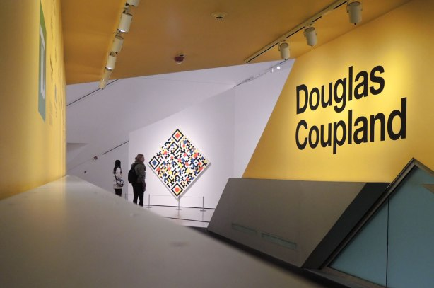 entrance to an exhibit at the Royal Ontario Museum featuring a large yellow wall with the name Douglas Coupland in large black letters.  In the distance are two women standing in front of a painting that is hung on point.
