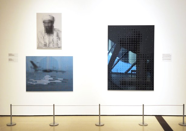 three paintings hanging on a wall in an art exhibit.  One is of Osama bin Laden and the other two are 9/11 related, New York .