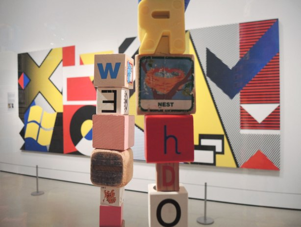 In the background is a large painting of geometric abstract shapes in yellows, reds and greys.  In the foreground is a close up of two stacks of blocks.  The blocks are old children's wooden building blocks but they are alll different.  Three have letters of the alphabet on them, one has a picture of a birds nest.