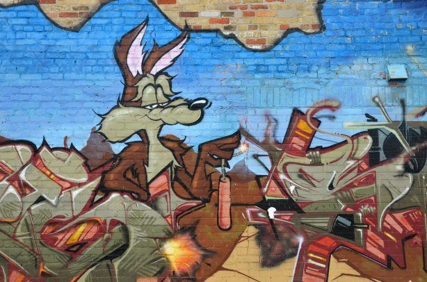 street art painting of Wile E. Coyote from the looney tunes cartoon.  He has a smug look on his face and he is holding a lit stick of dynamite.