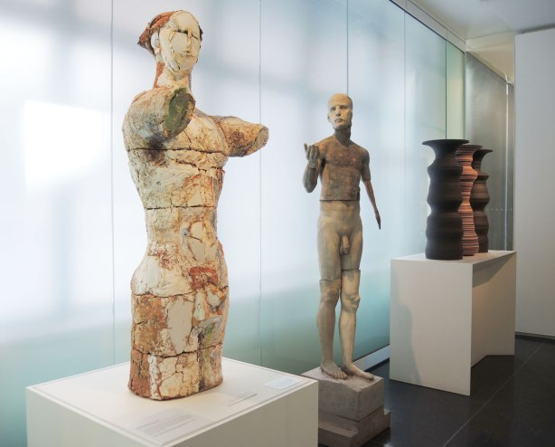 Three sculptures in a museum.  The one on the left is a naked man from mid-thigh to the top of the head, although the arms are only stumps.  The middle statue is also a naked man but he is all there.  He is composed of pieces of different men all put together.  The last sculpture is more abstract and it is hard to see in this photograph