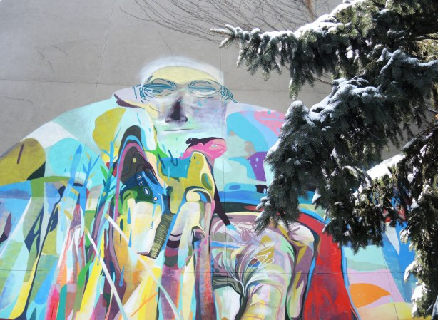 A graffiti face high on a grey wall, with a pine tree branch  partially obscuring it