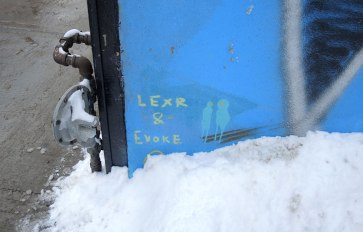 In the corner of a piece of graffiti with a blue background is a signature of the artists, in blovk letters, LEXR & EVOKE
