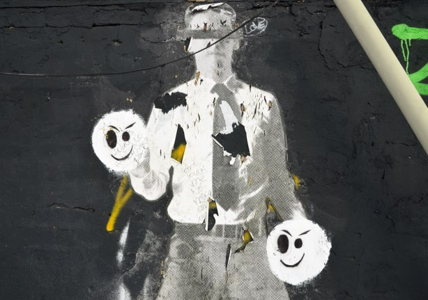 black and white paper graffiti of a man in grey pants, white shirt, and tie.  He has two black and white faces instead of hands.  Someone has scrawled words on the hands.