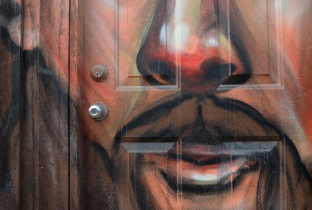 close up of man's face painted on a garage door.  You can see one ear, the nose and the mouth.