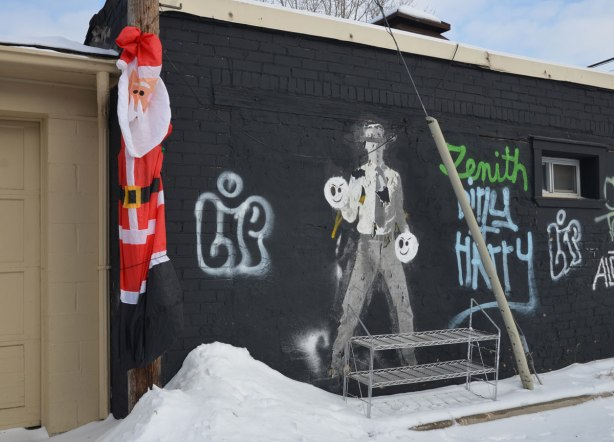 A deflated inflatable Santa Claus is hanging from a hydro pole in an alley beside a garage door with a graffiti man on it.