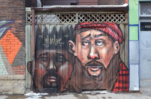 Street art painting of two men's heads.  Both have beards.  One is wearing a black crown and the other has a red hat and a red & black plaid shirt on