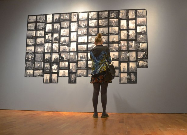 A girl is standing in front a photography exhibit where many black and white photos are grouped together to form one big picture.
