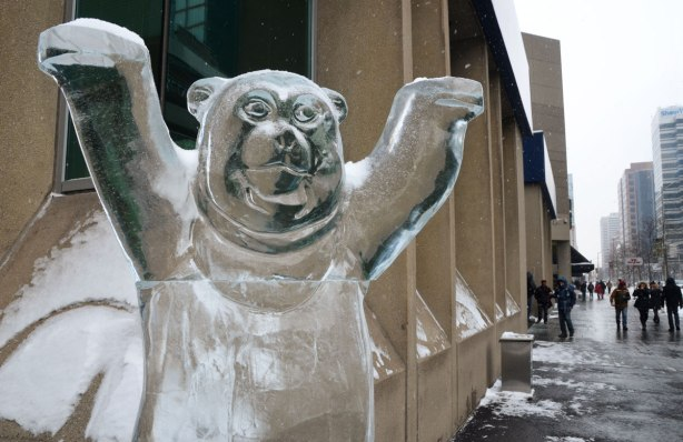 An ice sculpture of a bear with it's front paws raised, looms over the interesection of Yonge and Bloor.
