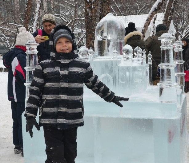 A boy is standing beside a sculpture