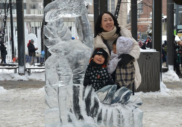 A mother with two little kids is posing with an ice sculpture.