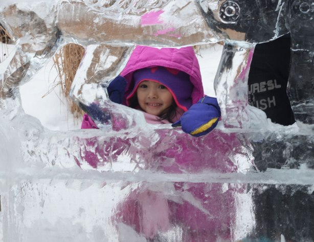 A little girl in a pink snow suit it peaking throw a whole in an ice sculpture
