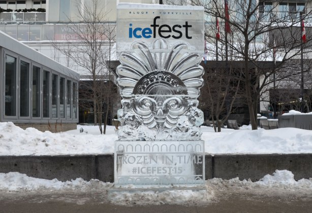 Ice sculpture beside a sidewalk.  The top part has the words Bloor Yorkville icefest and the bottom part has the words Frozen in time, icefest 15.   The middle section looks like a large face made of Egyptian motifs.