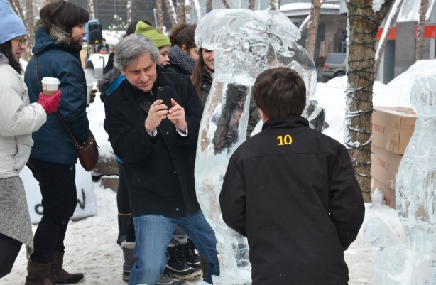 A father is taking a photograph of his son beside an ice sculpture