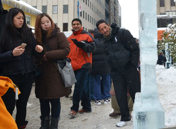A group of four people are standing around an ice sculpture.  They all have puzzled looks on their faces as though they can't figure out what the sculpture is supposed to be.