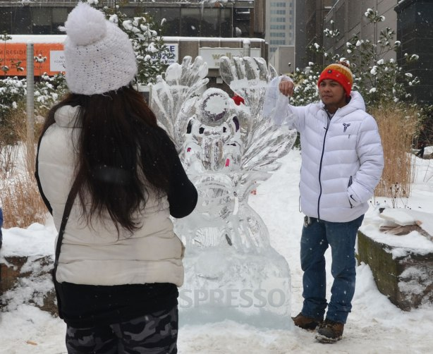 A man in a white parka is standing beside a sculpture with his elbow resting on it.  A woman in white coat and hat is taking his picture.