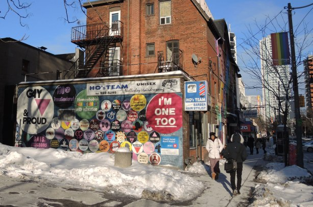 street scene in winter, looking along the sidewalk with a couple of people on it.  On the left is a three storey red brick building in the background.  In the foreground is a shorter building (seen from the side) covered with a mural depicting buttons with slogans and sayings on them.
