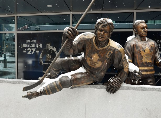 A bronze statue of Toronto Maple Leaf hockey player Darryl Sittler as he jumps over the boards and onto the ice, hockey stick in hand