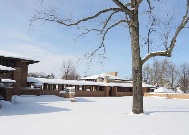 Exterior of the Darwin Martin House in winter showing the pergola and the conservatory. A low rise house designed by Frank Lloyd Wright in his prairie style. Lots of snow and blue sky.