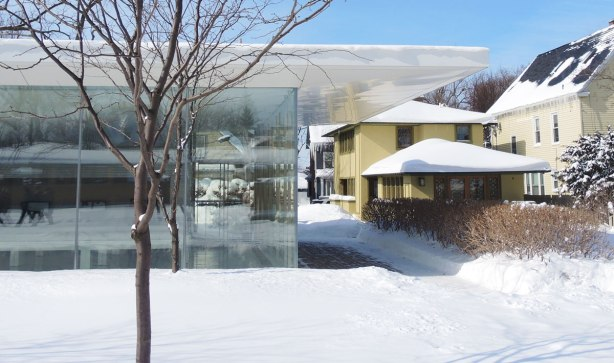 On the right is the back of a two storey yellow stucco house and on the left is part of a flat building with glass walls. Winter, lots of snow.