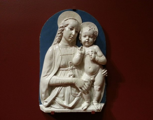 A white porcelain relief sculpture on a reddish wall. Mother and child, Mary and Jesus.