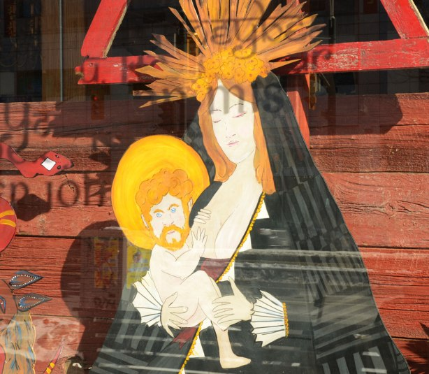 A picture of Mary and Jesus in a store window. Jesus is depicted as a middle age man.