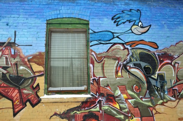 street art painting of the Looney Tunes cartoon character the roadrunner.  He is running past a window on a brick building.