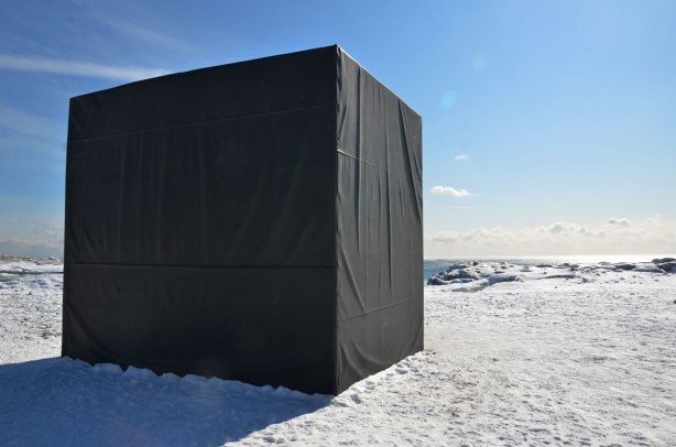 A large black box on a winter beach.  The box is large enough to fit several people inside it.